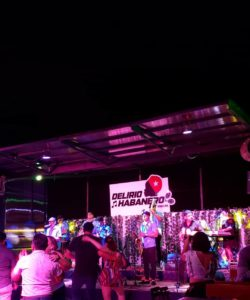 Outdoor night club with people dancing to a band