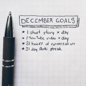 """A pen photographed above paper which says """"december language goals"""""""