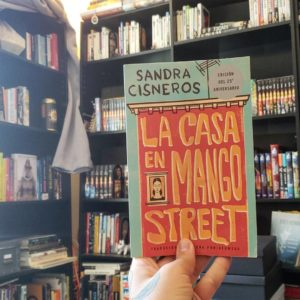 A hand holding the book La Casa En Mango Street in front of bookshelves
