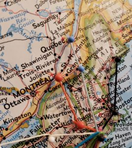 A map with pins and string between the cities of Quebec, Montreal, Boston, Providence, Hartford, and NYC