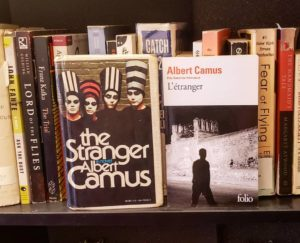 """Two versions of the Camus book """"the stranger"""", one in English and one in French, against a bookshelf"""