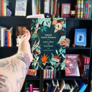 A hand holding a Spanish language novel in front of a book shelf