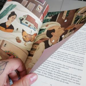 A hand turning through pages in a Spanish language novel with some illustrations showing