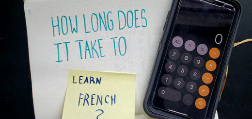 "The words ""how long does it take to learn French"" written on paper in marker with a calculator"