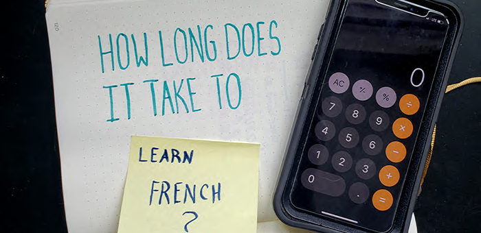 """The words """"how long does it take to learn French"""" written on paper in marker with a calculator"""