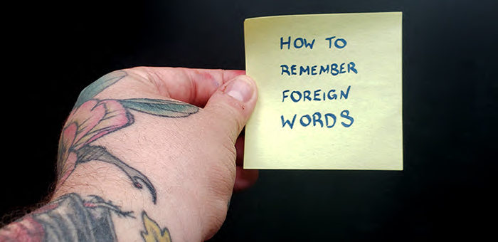 "A hand holding a sticky note that says ""how to remember foreign words"""