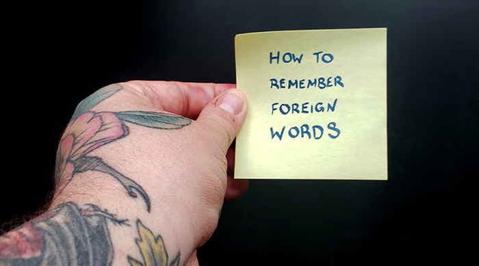 """A hand holding a sticky note that says """"how to remember foreign words"""""""