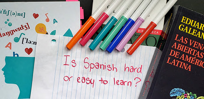 """The words """"Is Spanish hard or easy to learn"""" written on paper with markers"""