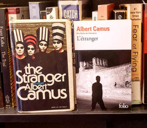 Two covers of the French book The Stranger: one in English, one in French