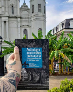 A hand holding a French book in front of palm trees and an old-looking church