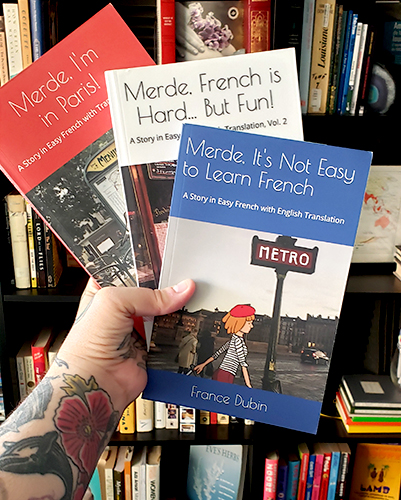 An image of the Merde trilogy French books being held together