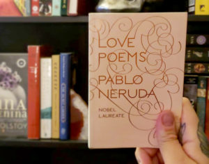 The bilingual Spanish poetry book by Pablo Neruda being held in the author's hand, which is smaller than a post card